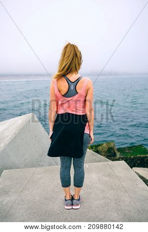 Back view of unrecognizable young woman watching the sea