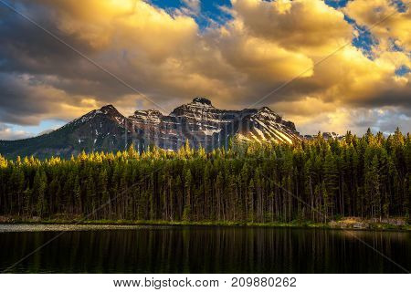 Scenic sunset over deep forest along the Herbert Lake in Banff National Park, with snow-covered peaks of canadian Rocky Mountains in the background.