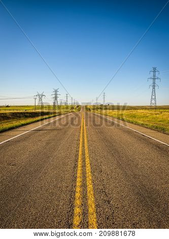 High electricity Pillars with , transmission lines along an empty road in Alberta, Canada