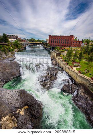 SPOKANE, WASHINGTON, USA - JULY 4, 2017 : Falls and the Washington Water Power building along the Spokane river viewed from the Monroe Street Bridge, in Spokane, Washington.