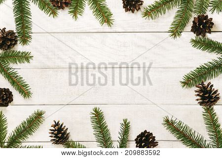 White wooden Christmas background. Border decorated fir branches and pin cones. Copy space for holiday greetings. lovely  xmas festive card. Top view. Flat. Happy New Year