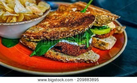 A sandwich made with breaded eggplant on toast and served with a side of potato chips.