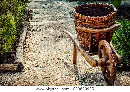 An old wood and wicker wheelbarrow sitting near a garden in Williamsburg Virginia.