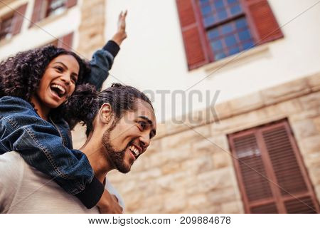 Man carrying his girlfriend on his back walking on the street. Woman piggy riding on man in a cheerful mood.