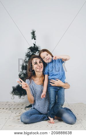 Mother And Little Daughter Decorating Christmas Tree