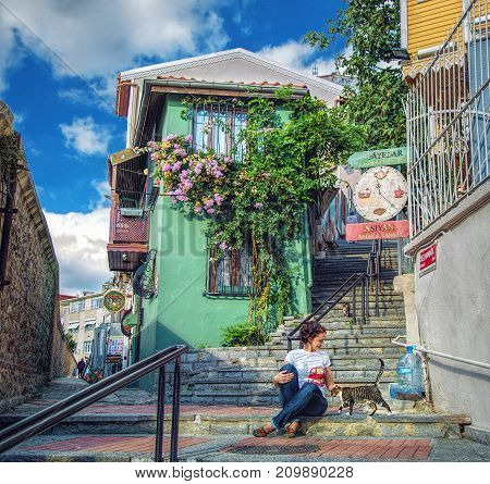 ISTANBUL TURKEY: Pretty girl sitting with cat on stair of old street with cute green house in Uskudar district on October 3 2017