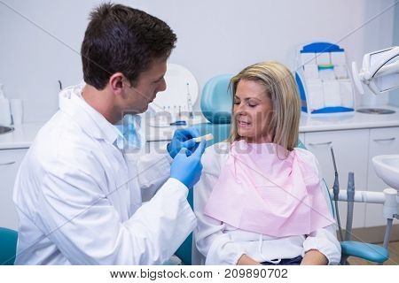 Side view of young doctor showing dental mold to patient at dental clinic