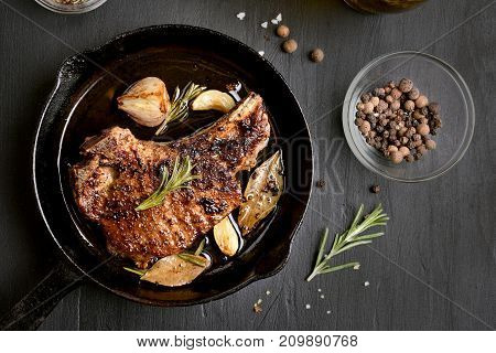 Pork steak in frying pan over dark background top view