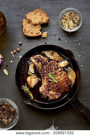 Grilled meat. Roasted pork steak in frying pan over dark background top view