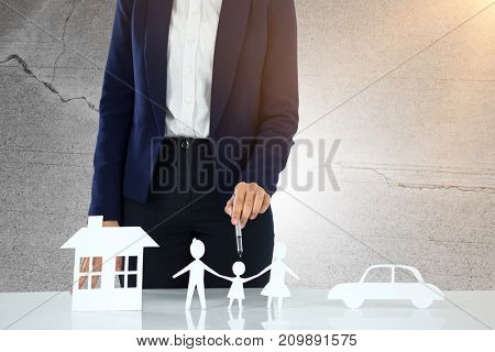 woman drawing a car, a family and a house against concrete wall with crack