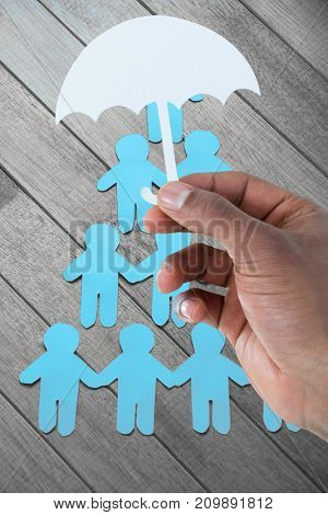 hand holding an umbrella in paper against paper cut out figures forming human pyramid on table