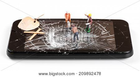 construction worker figurines repairing broken smartphone screen