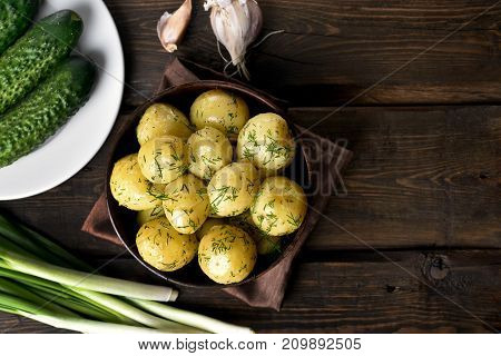 Boiled potatoes with dill in bowl on wooden background with copy space top view