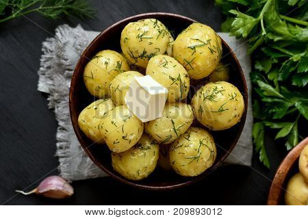 Tasty new boiled potatoes with dill and butter in bowl top view close up.