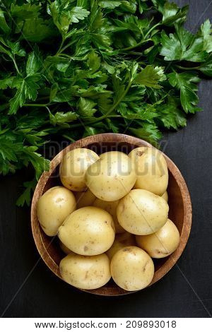Fresh raw potatoes in wooden bowl and green parsley on dark background top view