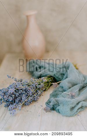glass cup of tea with raspberries on the background of a bouquet of lavender wrapped in a scarf