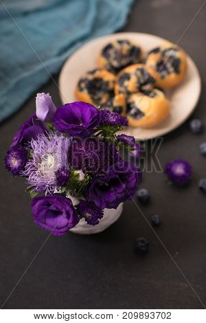 a plate of cakes with blueberries on a decorated table on which stands a vase of flowers