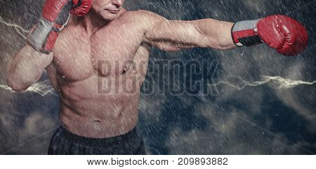 Bald boxer in fighting stance against digitally generated image of powder