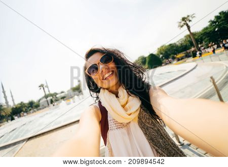 A cheerful travel girl with a backpack doing selfie. Glasses, dentist with white teeth, open smile, looking at camera