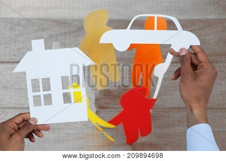 man holding a car and a house in paper against colorful paper figures forming circle on table