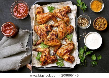 Grilled chicken wings on baking tray over dark background top view