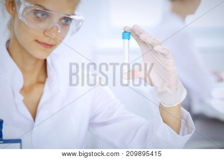 Female scientific researcher in laboratory studying substances or blood sample. Medicine and science concept.