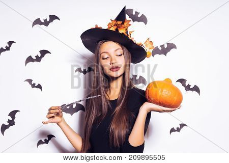 a young beautiful gothic girl in the shape of a witch in halloween, a big black hat decorated with yellow leaves, holding a pumpkin