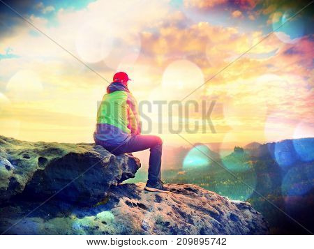 Alone Tourist Take A Rest. Hiker  In Green Black Jacket Sitting On The Rocky Peak While Enjoying Vie