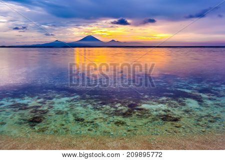 The shallow waters of Gili Trawangan island on the background of the Gunung Agung mountain Indonesia. Transparent calm Bali sea at evening.