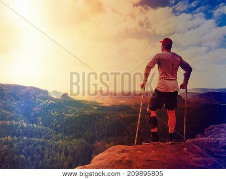 Hiker In Grey T-shirt, Medicine Crutch And  Leg Fixed In Immobilize Achieved Mountain Peak. Man Has