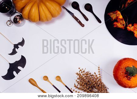 composition for decorating a house on halloween, on a white table lie yellow and orange pumpkins, burning scented candles, yellow leaves and wooden spoons