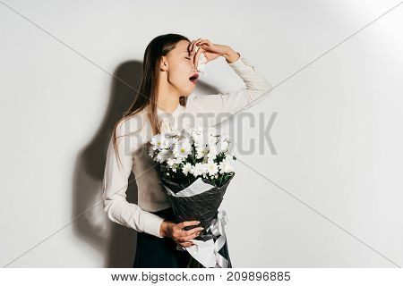 a young girl holds a large bouquet of white flowers in her hands and sneezes because she is allergic