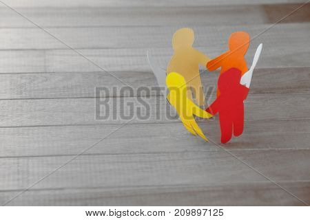 High angle view of colorful paper figures forming circle on wooden table