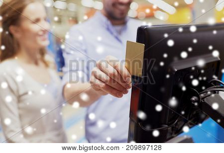 shopping, technology, consumerism and people concept - happy couple at grocery store or supermarket self-checkout swiping customer card over snow