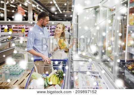 sale, consumerism and people concept - happy couple with shopping cart buying frozen food at grocery store or supermarket over snow