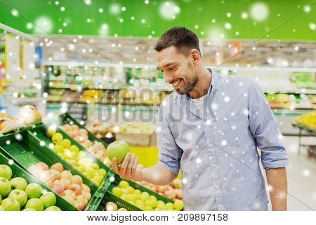 shopping, food sale, consumerism and people concept - happy man buying green apples at grocery store or supermarket over snow