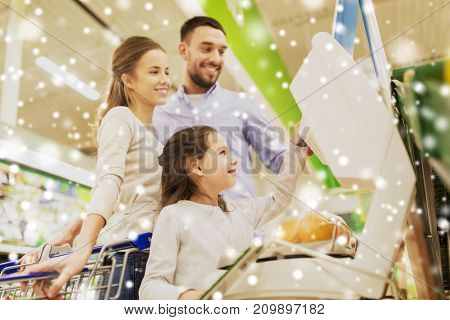shopping, sale, consumerism and people concept - happy family with child weighing oranges on scale at grocery store or supermarket over snow