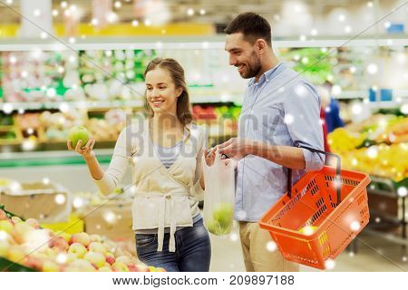 shopping, food sale, consumerism and people concept - happy couple buying apples at grocery store or supermarket over snow