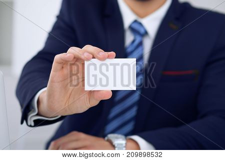 Unknown businessman or lawyer  giving a business card while sitting at the table, close-up. He offering partnership and success deal.