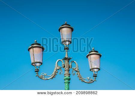 Streetlight vintage style retro Lamppost on blue sky background.