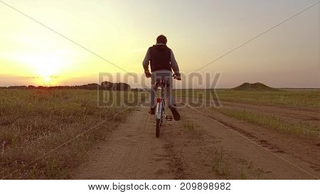 Boy teenager riding a bicycle. Boy teenager riding a bicycle goes to nature along path steadicam shot video motion