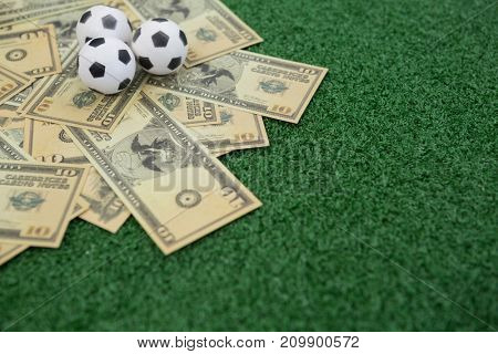 Footballs and currency notes arranged on artificial grass