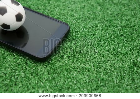 Close-up of football and mobile phone on artificial grass