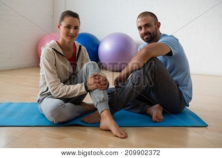 Portrait of female student and yoga instructor relaxing in health club