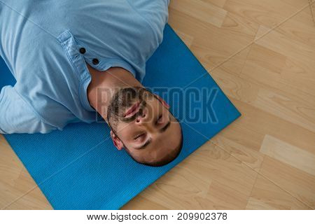 High angle view of yoga instructor exercising while lying on mat in yoga studio