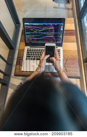 Investor checking the stock market on laptop and smart phone