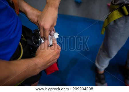 Cropped hand of woman taking chalk powder from trainer in gym