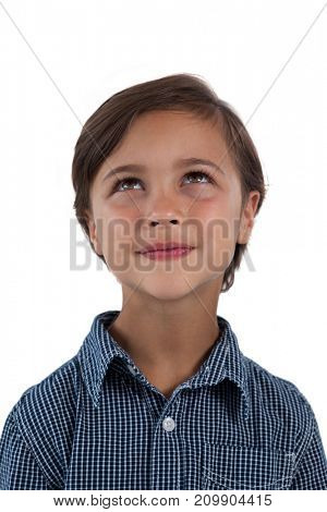 Thoughtful boy standing against white background