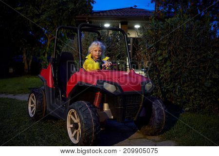 Little girl in yellow jacket sits in red buggy car in house yard.