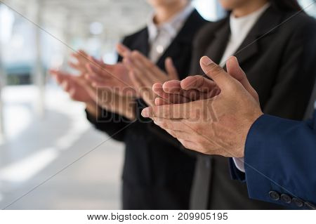 Three business people clap their hands to congratulate the signing of an agreement or contract between their firms companies enterprises. success dealing greeting and partner concept.